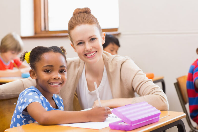 Female teacher at desk with female elementary student smiling at camera